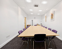 Image of our conference room facilities with large rectangular meeting table and 14 chairs