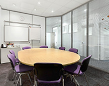 Photograph of our conference room facilities with large oval table and eight chairs