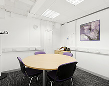Image of one of our meeting rooms with a round table and four chairs